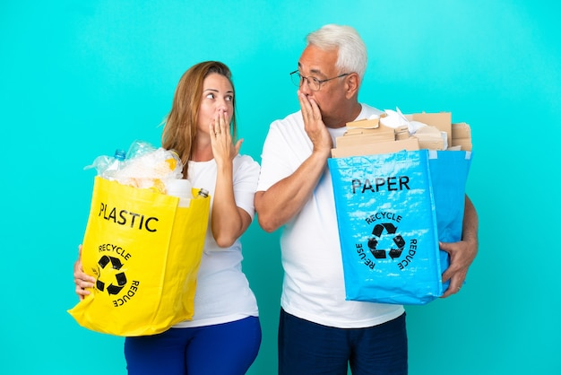 Пара среднего возраста держит мешки для переработки бумаги и пластика на белом фоне, прикрывая рот руками за то, что сказала что-то неуместное