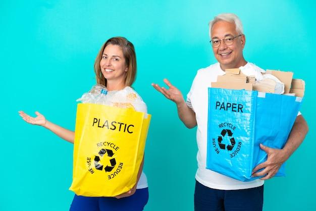 Пара среднего возраста держит мешки для переработки, полные бумаги и пластика, изолированные на белом фоне, протягивая руки в сторону, приглашая приехать