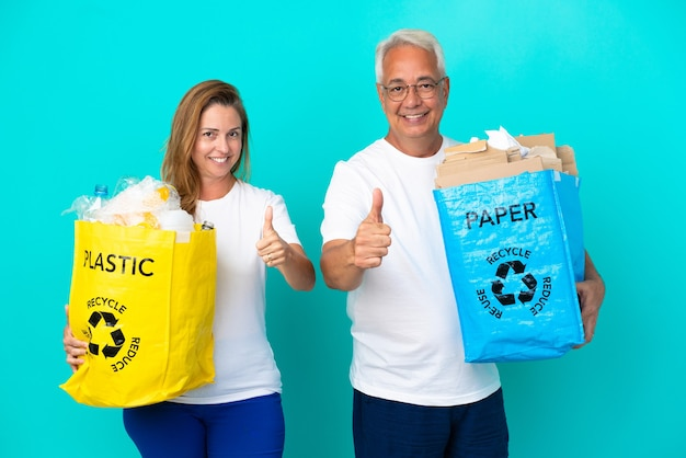 Пара среднего возраста держит мешки для переработки, полные бумаги и пластика, изолированные на белом фоне, показывая большой палец вверх, потому что произошло что-то хорошее