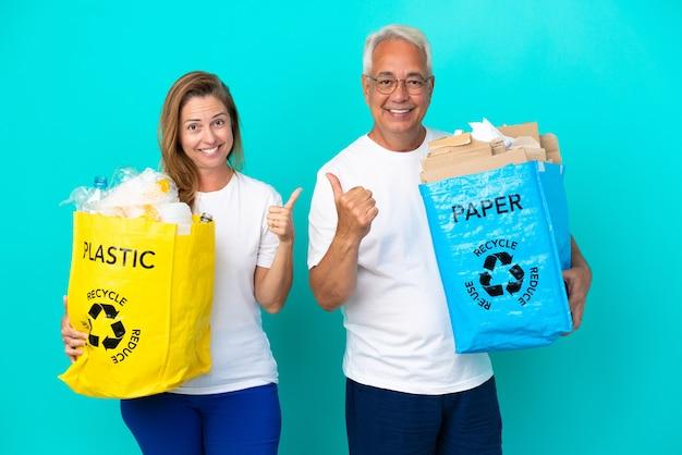 Пара среднего возраста держит мешки для переработки, полные бумаги и пластика, изолированные на белом фоне, показывает палец вверх обеими руками и улыбается