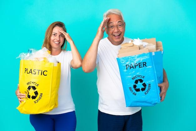 Пара среднего возраста, держащая пакеты для переработки, полные бумаги и пластика, изолированные на белом фоне, только что что-то поняла и намеревается решить
