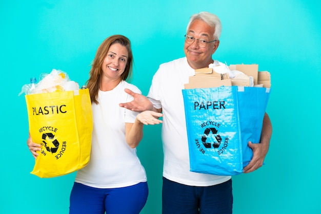 Пара среднего возраста держит мешки для рециркуляции, полные бумаги и пластика, изолированные на белом фоне, сомневаясь, поднимая руки и плечи