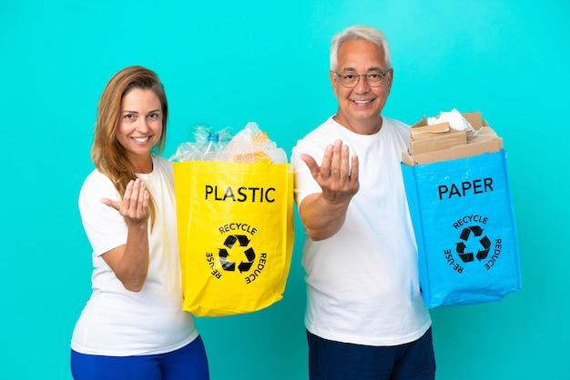 Пара среднего возраста держит мешки для рециркуляции, полные бумаги и пластика, изолированные на белом фоне, приглашая прийти с рукой. счастлив что ты пришел