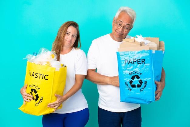 Пара среднего возраста держит мешки для переработки, полные бумаги и пластика, изолированные на белом фоне, делая жест сомнения, поднимая плечи