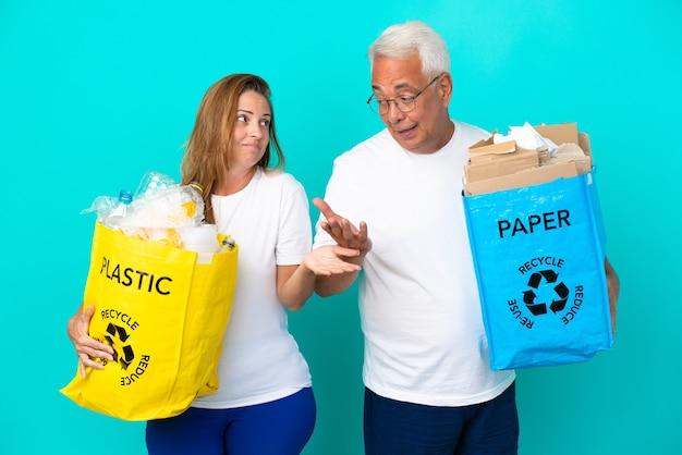 Пара среднего возраста держит мешки для переработки, полные бумаги и пластика, изолированные на белом фоне, делая неважный жест, поднимая плечи