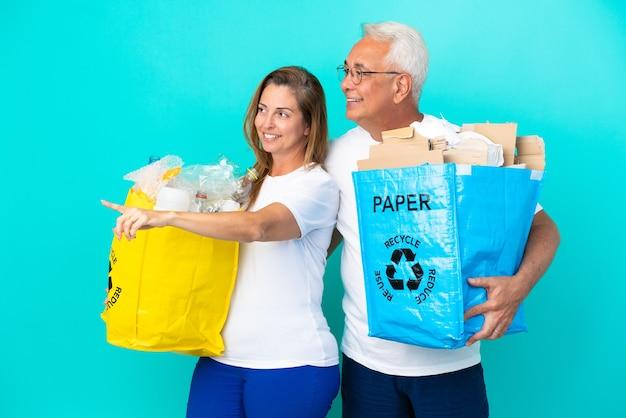 Пара среднего возраста держит мешки для переработки, полные бумаги и пластика, изолированные на белом фоне, указывая в сторону, чтобы представить продукт