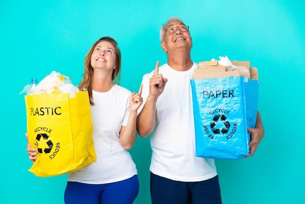 Пара среднего возраста держит мешки для переработки, полные бумаги и пластика, изолированные на белом фоне, указывая указательным пальцем - отличная идея