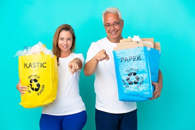 Пара среднего возраста держит мешки для вторичной переработки, полные бумаги и пластика, изолированные на белом фоне, с уверенным выражением лица указывает пальцем на вас