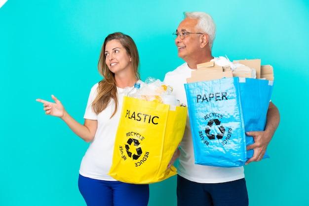 Пара среднего возраста держит мешки для переработки, полные бумаги и пластика, изолированные на белом фоне, представляя идею, глядя в сторону