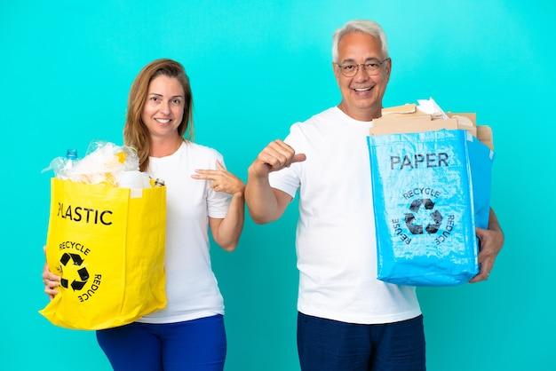Пара среднего возраста держит мешки для переработки, полные бумаги и пластика, изолированные на белом фоне, гордые и самодовольные в любви к себе концепции