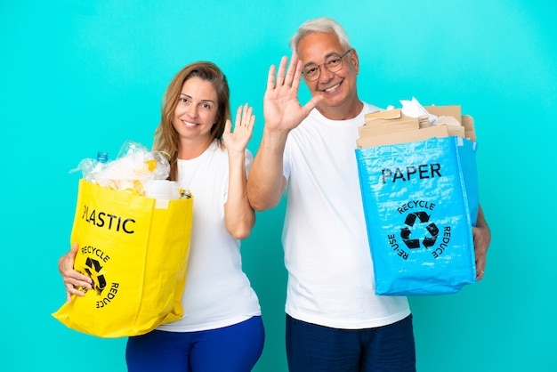 Пара среднего возраста держит мешки для переработки, полные бумаги и пластика, изолированные на белом фоне, салютуя рукой с счастливым выражением лица