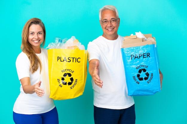 Пара среднего возраста держит мешки для переработки, полные бумаги и пластика, изолированные на белом фоне, пожимая руки для заключения хорошей сделки