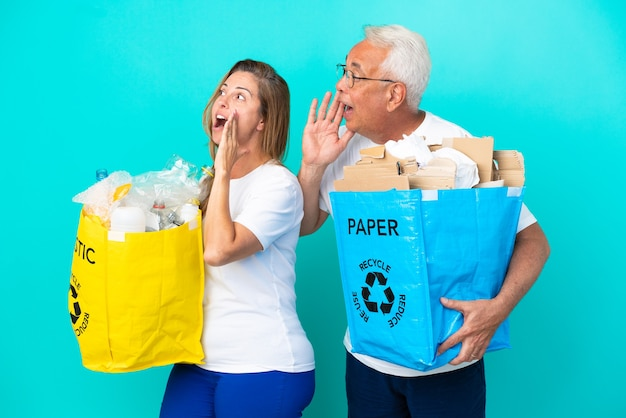 紙とプラスチックでいっぱいのリサイクルバッグを持っている中年のカップルは、横に大きく開いた口で叫んで白い背景で隔離