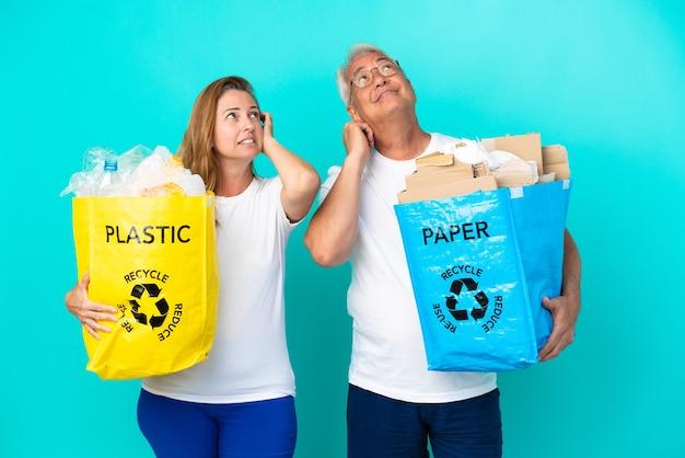 Пара среднего возраста держит мешки для переработки, полные бумаги и пластика, изолированные на белом фоне, думая об идее, почесывая голову