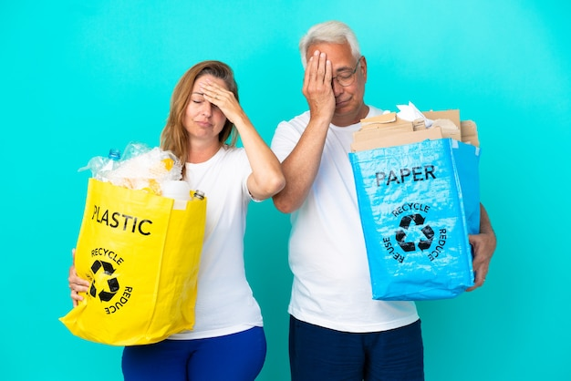 Пара среднего возраста держит мешки для переработки, полные бумаги и пластика, изолированные на белом фоне с удивленным и шокированным выражением лица