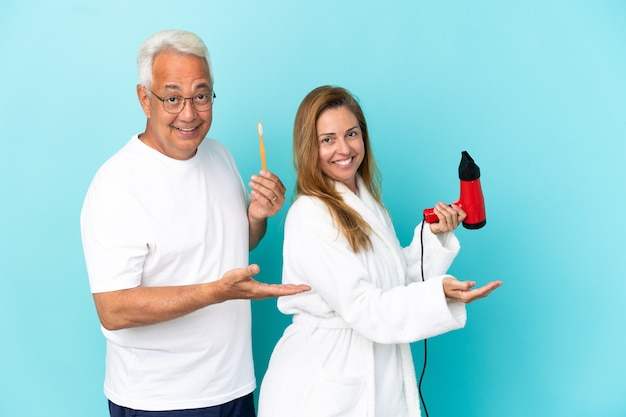 Пара среднего возраста держит сушилку и зубную щетку, изолированные на синем фоне, протягивая руки в сторону, приглашая прийти