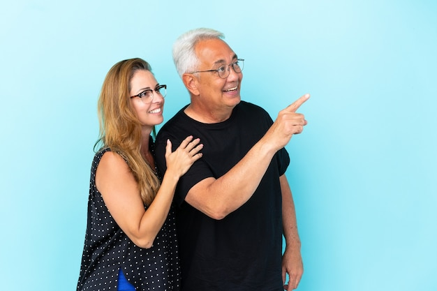 Middle age couple isolated on blue background pointing finger to the side and presenting a product