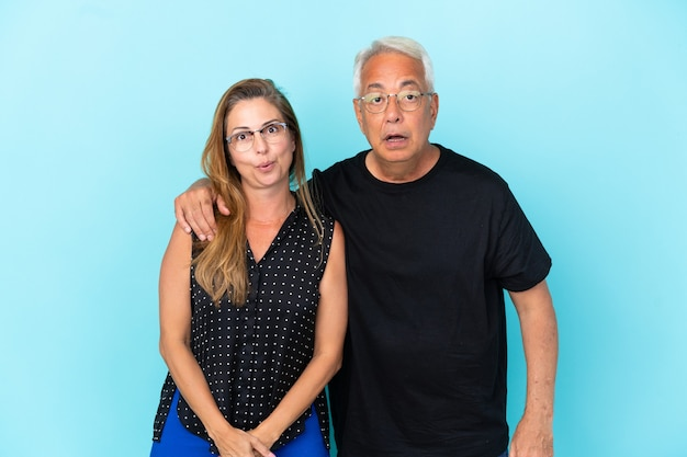 Middle age couple isolated on blue background with surprise facial expression