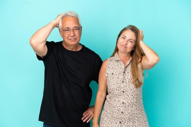 Пара среднего возраста, изолированные на синем фоне с выражением разочарования и непонимания