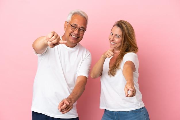Пара среднего возраста, изолированная на розовом фоне, с уверенным выражением лица указывает пальцем на вас