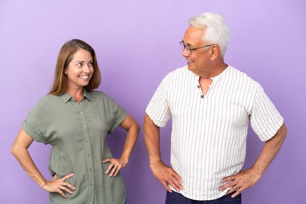 Пара среднего возраста, изолированные на фиолетовом фоне, счастливы и улыбаются