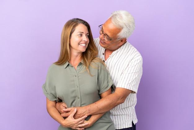 Пара среднего возраста, изолированные на фиолетовом фоне, обниматься