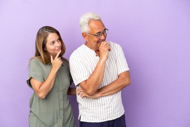 Пара среднего возраста, изолированные на фиолетовом фоне, глядя в сторону