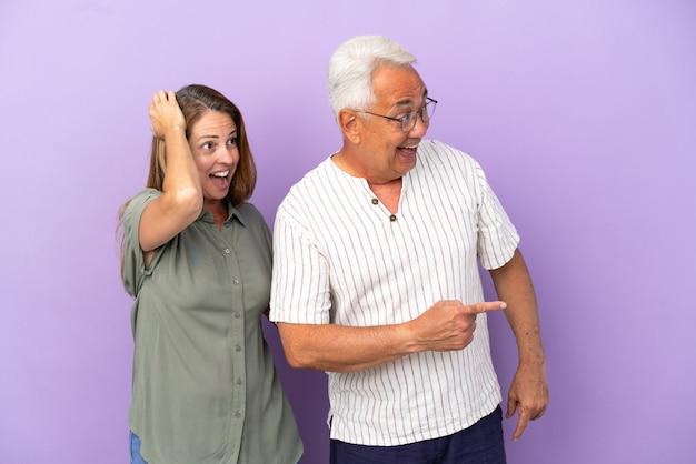 Пара среднего возраста изолирована на фиолетовом фоне, указывая пальцем в сторону с удивленным лицом