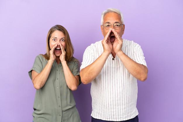 Пара среднего возраста изолирована на фиолетовом фоне, кричит и объявляет что-то