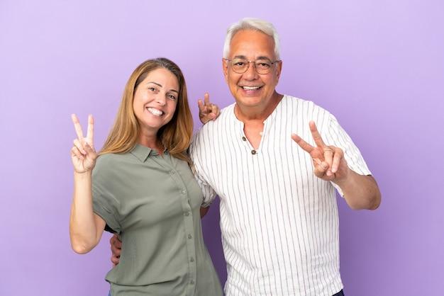 Пара среднего возраста, изолированные на фиолетовом фоне, улыбаясь и показывая знак победы
