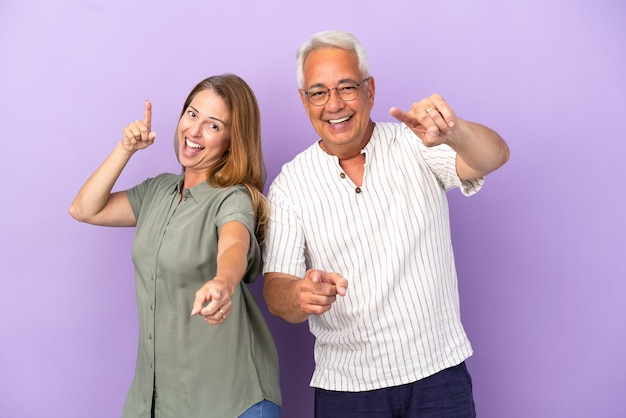 Middle age couple isolated on purple background points finger at you with a confident expression