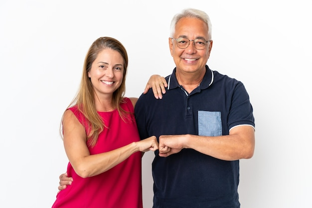 Middle age couple isolated on white background bumping fists