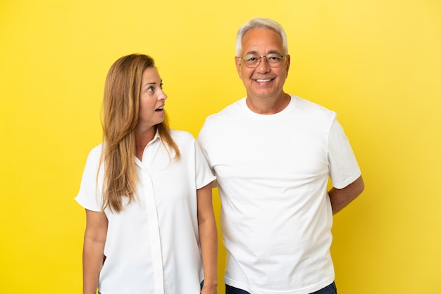 Middle age couple isolated on yellow background with surprise facial expression