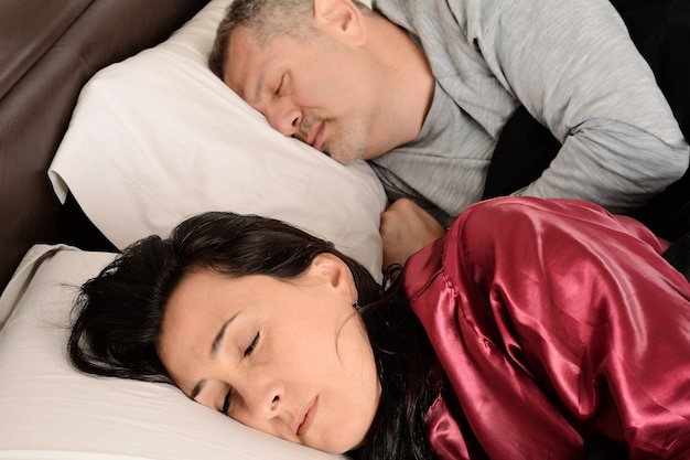 Middle age couple in sleeping together