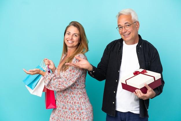 買い物袋と青い背景に分離されたギフトと中年のカップルは、来て招待するために手を横に伸ばします