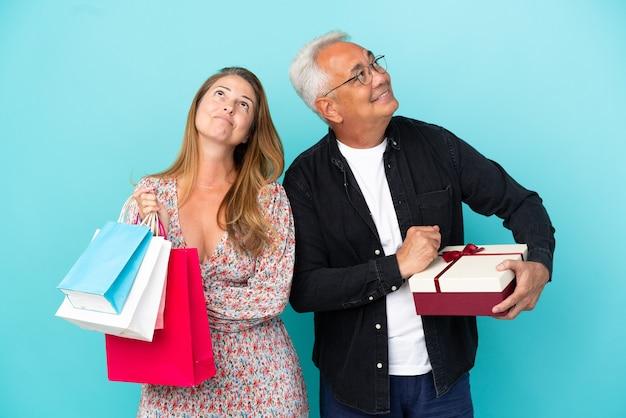 Пара среднего возраста с хозяйственной сумкой и подарком, изолированные на синем фоне, глядя вверх, улыбаясь