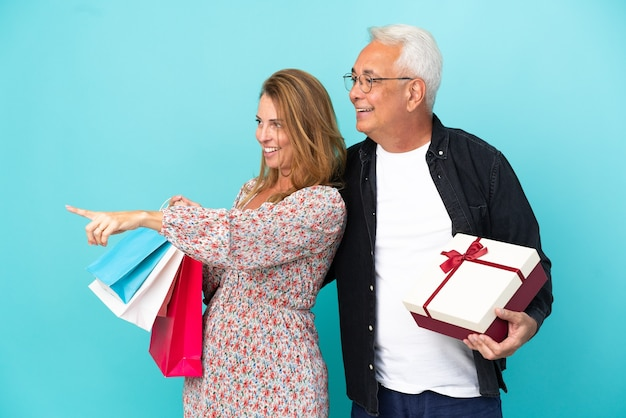 製品を提示する側を指している青い背景に分離されたショッピングバッグとギフトと中年カップル