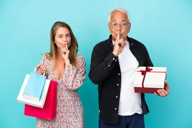 Пара среднего возраста с хозяйственной сумкой и подарком, изолированные на синем фоне, показывая знак жеста молчания, положив палец в рот
