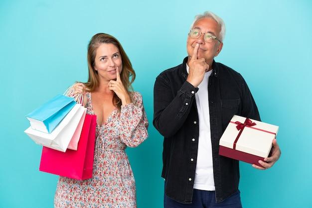 Пара среднего возраста с хозяйственной сумкой и подарком, изолированные на синем фоне, улыбаясь со сладким выражением лица