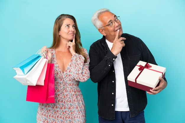 Middle age couple with shopping bag and gift isolated on blue background thinking an idea while looking up