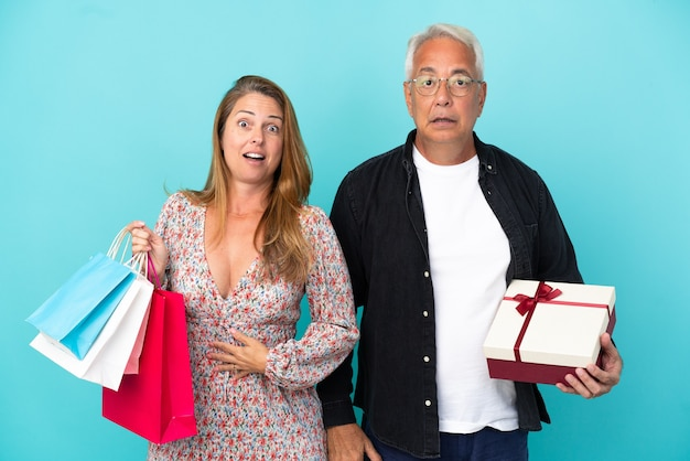 Middle age couple with shopping bag and gift isolated on blue background with surprise and shocked facial expression