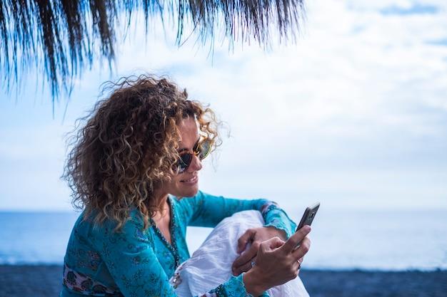 中年の巻き毛の女性のテクノロジー中毒の共有とソーシャルメディアネットワークを読んで、プライバシーのない彼女の人生を彼のアカウントに投稿します-どこでも屋外休暇のビーチのコンセプトを使用してインターネット中毒