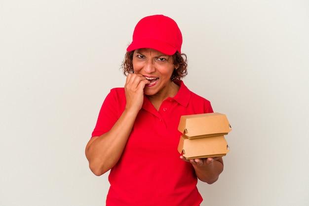 中年の配達の女性は、白い背景の爪を噛んで孤立したブルガーを取り、神経質で非常に心配しています。