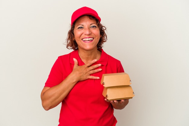 白い背景で隔離のブルガーを取っている中年配達の女性は、胸に手を置いて大声で笑います。