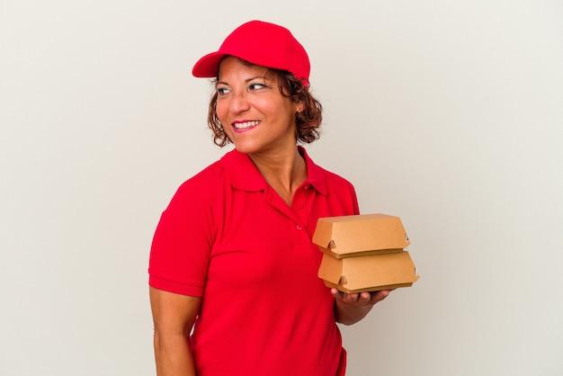 白い背景で隔離のブルガーを取っている中年の配達の女性は、笑顔、陽気で楽しい脇に見えます。