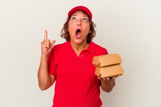 口を開けて逆さまを指している白い背景で隔離のブルガーを取っている中年配達の女性。