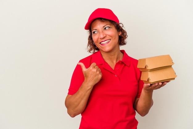 白い背景のポイントで隔離されたブルガーを親指の指で離して、笑ってのんきな中年配達の女性。