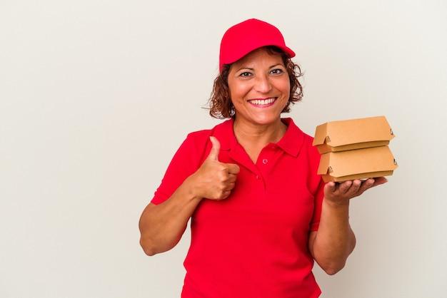 笑顔と親指を上げて白い背景で隔離のブルガーを取る中年配達の女性