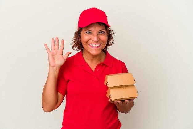 指で5番を示す陽気な笑顔の白い背景で隔離のブルガーを取っている中年配達の女性。