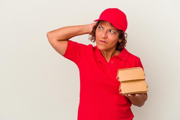 頭の後ろに触れて、考えて、選択をする白い背景で隔離のブルガーを取る中年配達の女性。